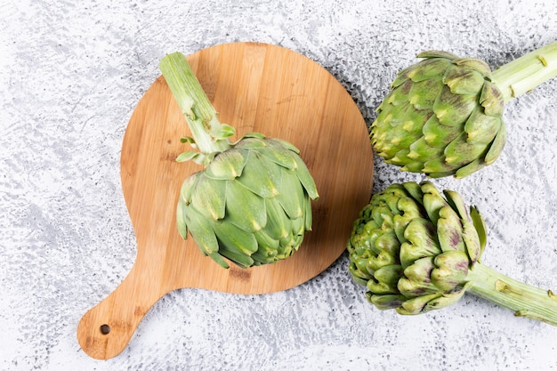 Top view artichokes in cutting board on light gray background. vertical