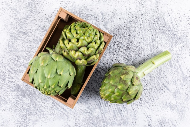 Top view artichokes in wooden box on light gray background. horizontal