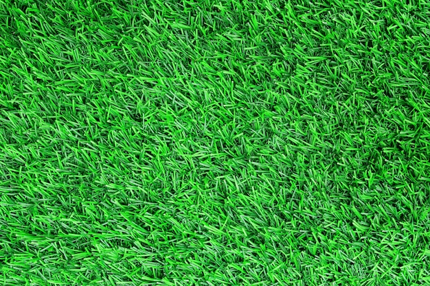 Top view of artificial green grass texture background.