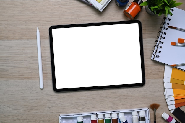 Top view of artist or designer workspace with digital tablet