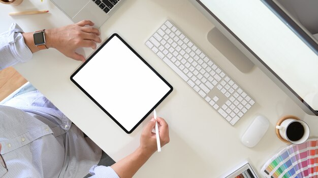 Top view of an artist drawing something on graphic tablet at the office