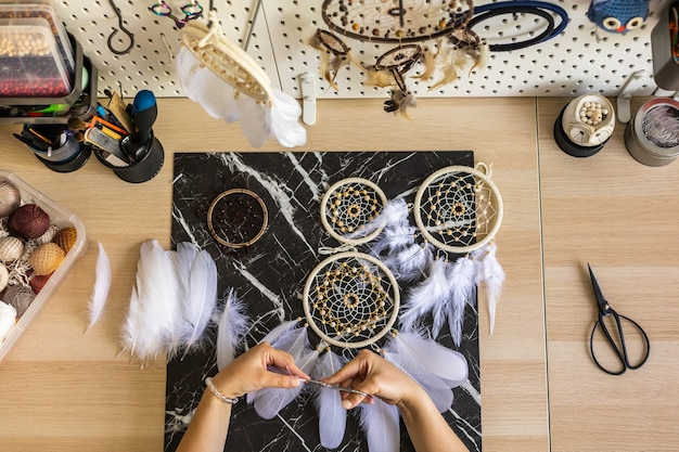 Top view artistic female hands creating dreamcatcher with feathers and thread in circle pov shot