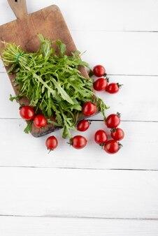Вид сверху листья рукколы лежат рядом с красными помидорами на столе