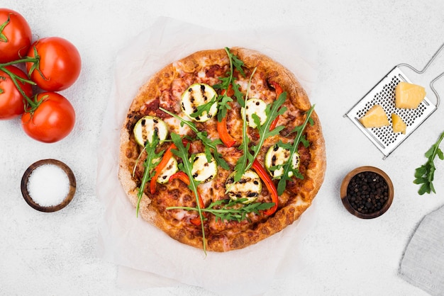 白い背景の上のトップビュールッコラピザ