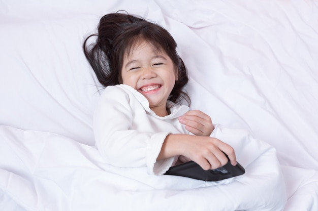 Top view of asia little kid having fun playing smartphone lying on a bed in the morning on soft pillows laughing feels happy.