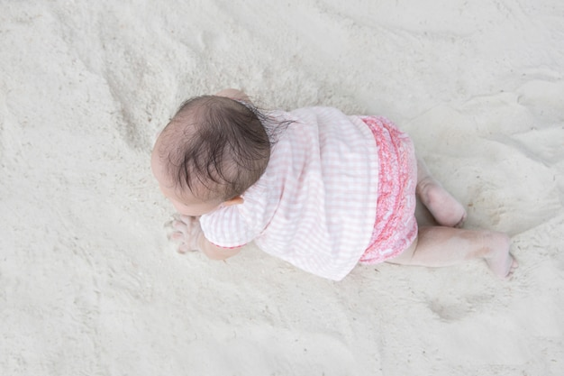 Top view of asian baby crawling on the sand