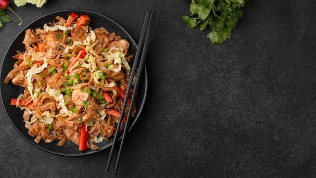 Vista dall'alto del piatto asiatico con le bacchette e lo spazio della copia