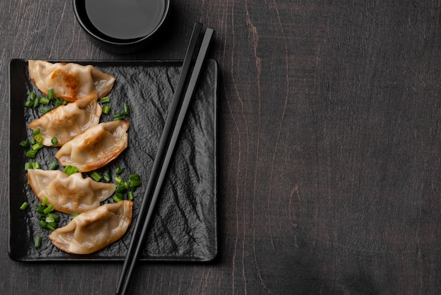 Top view of asian dumplings dish on slate with copy space