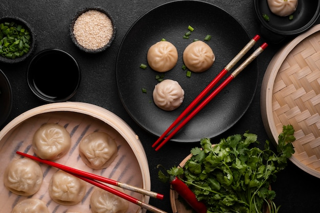 Top view of asian dumplings with chopsticks and herbs