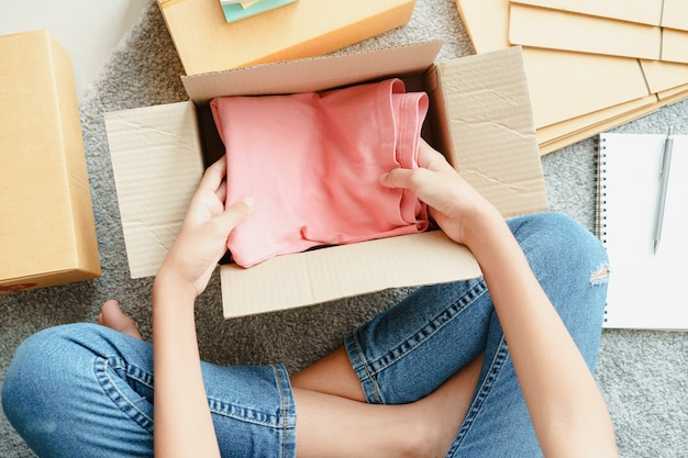 Top view of asian girl is preparing pink clothes down inside a parcel box according to the customer order.