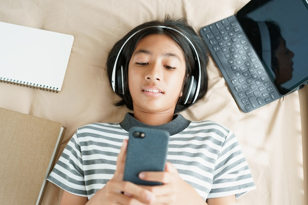 Top view of asian little girl is lying listening to music on her smartphone