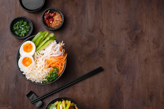 Top view of asian noodles with eggs and copy space