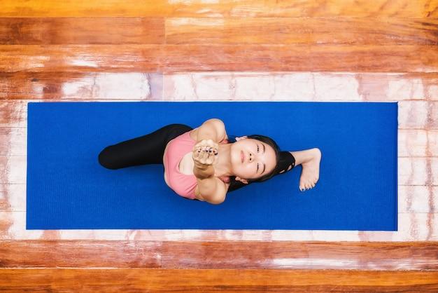 上面図covid19が健康または瞑想で発生したときに自宅からヨガを練習しているアジアの女性