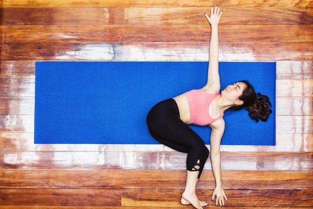 上面図covid19が健康に発生したときに自宅からヨガを練習しているアジアの女性