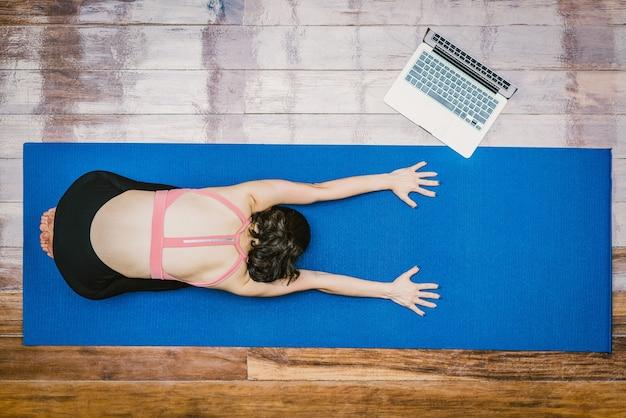 トップビューcovid19の発生時にラップトップで自宅からヨガを練習しているアジアの女性