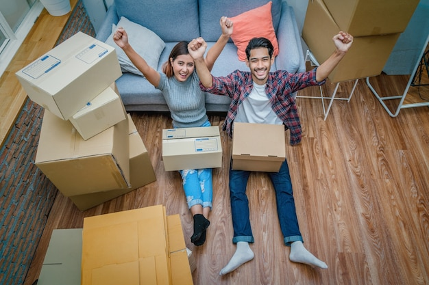 Top view asian young couple are glad after successfull packing the cardboard box