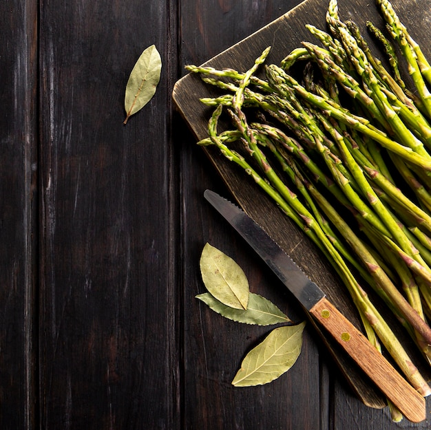 Top view of asparagus with knife and bay leaves