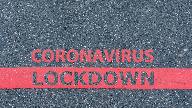 Top view of the asphalt road with red line and text coronavirus lockdown, restriction or safety warning concept