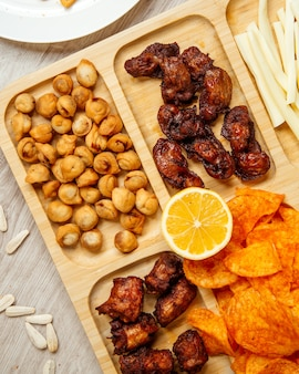 Top view of assorted beer snacks as fried dushbara grilled chicken and potato chips on a wooden board