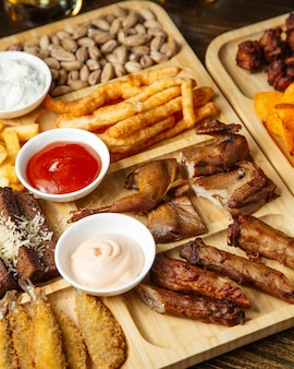 Top view of assorted beer snacks as roasted quails  french fries   pistachios and  potato chips with sauces on a wooden board