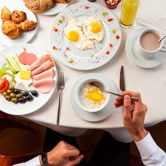 Top view assorted breakfast with oatmeal and fried eggs, human hand in white plate