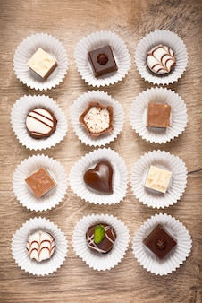 Top view on assorted chocolate pralines on wood