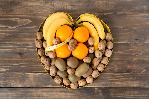 Top view of assorted fruit and dried fruits forming a heart on a dark wooden table. healthy eating and wellness concept.