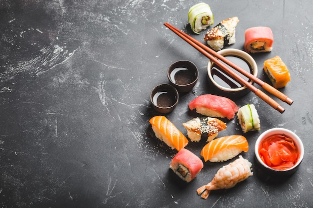 Top view of assorted mixed japanese sushi set with rolls, nigiri, soy sauce, ginger, chopsticks, two cups of traditional sake on black concrete background. asian dinner or lunch, free space for text