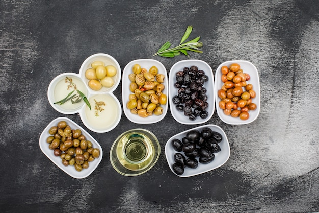 Top view assorted olives and olive oil in white plates and glass jar with olive tree branch on dark grey grunge surface. horizontal