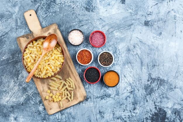 Vista dall'alto di pasta assortita in una ciotola con spezie, cucchiaio di legno su intonaco grigio e sfondo tagliere. orizzontale
