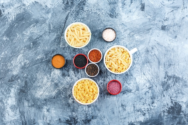 Top view assorted pasta in bowls with spices on grey plaster background. horizontal