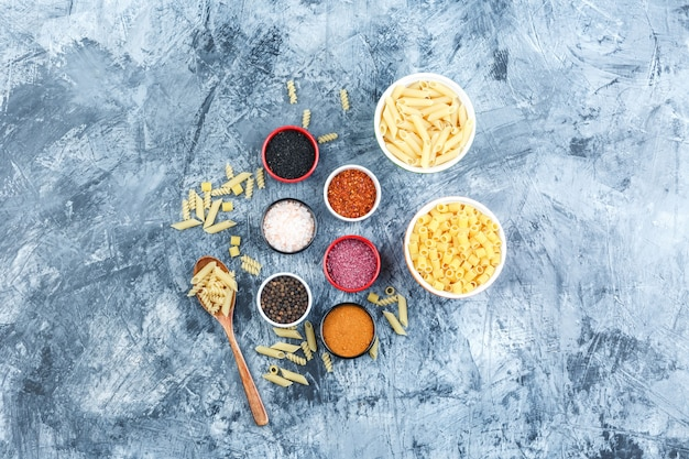 Top view assorted pasta in bowls and wooden spoon with spices on grey plaster background. horizontal
