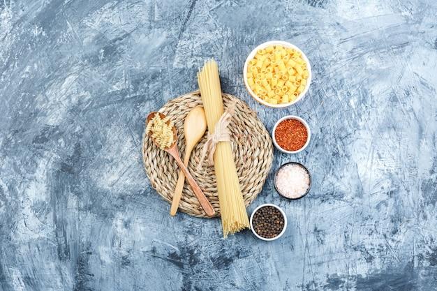 灰色の石膏と枝編み細工品のプレースマットの背景にスパイスとボウルと木のスプーンでさまざまなパスタの上面図。水平
