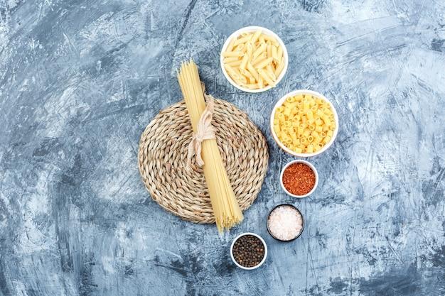 灰色の石膏と枝編み細工品のプレースマットの背景にスパイスを入れたボウルのトップビュー各種パスタ。水平