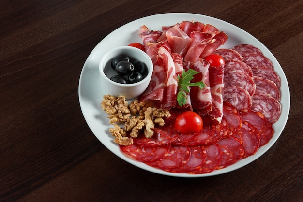 Top view of an assorted salami meat plate served with black olives and walnuts on the table