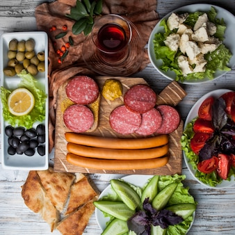 Top view assorted sausages with assorted olives and vegetables and glass of tea in board cookware