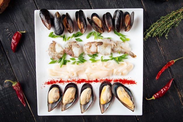 Top view on assorted seafood platter on the dark wooden table
