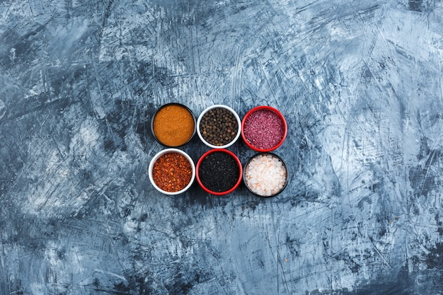 Top view assorted spices in small bowls on grey plaster background. horizontal
