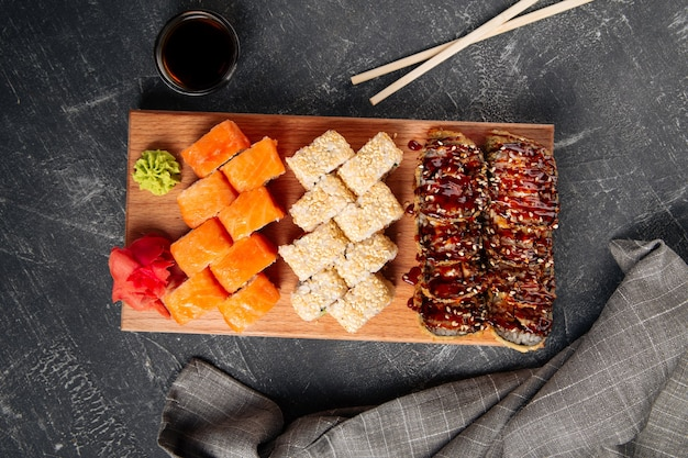 Top view on assorted sushi rolls on a wooden board with wasabi and soy sauce