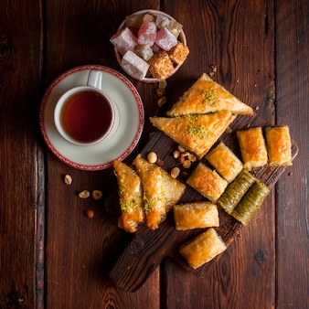 Top view assorted turkish baklava with cup of tea and turkish delight in wooden plank