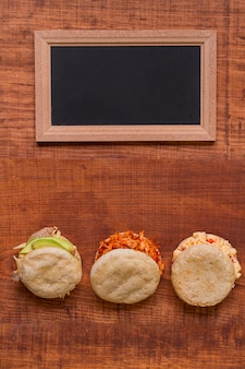 Top view of assortment of arepas with chalkboard