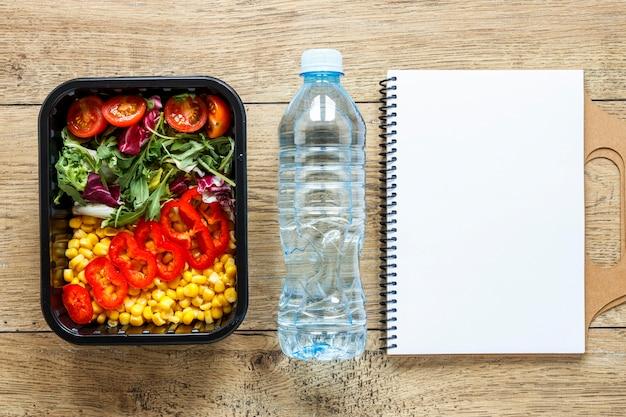 Vista dall'alto assortimento di alimenti in lotti cucinati con taccuino vuoto e acqua