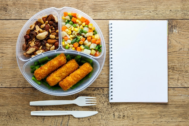 Top view assortment of batch food cooked with empty notebook