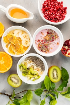 Top view assortment of bowls with organic fruits