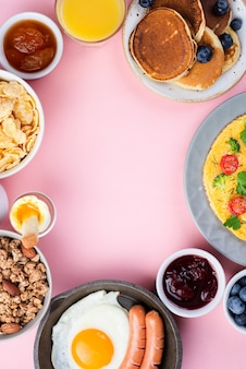 Top view of assortment of breakfast food with egg and sausages