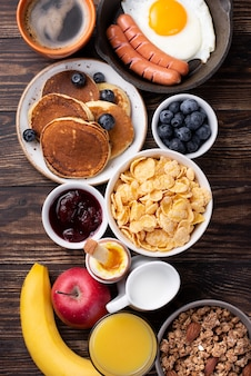 Top view of assortment of breakfast food with milk and orange juice