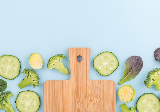 Top view assortment of cucumber slices with chopping board