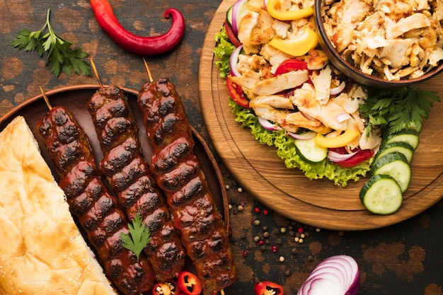 Vista dall'alto dell'assortimento di deliziosi kebab con verdure ed erbe aromatiche