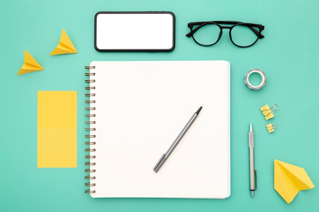 Top view assortment of desk elements with empty notebook and phone