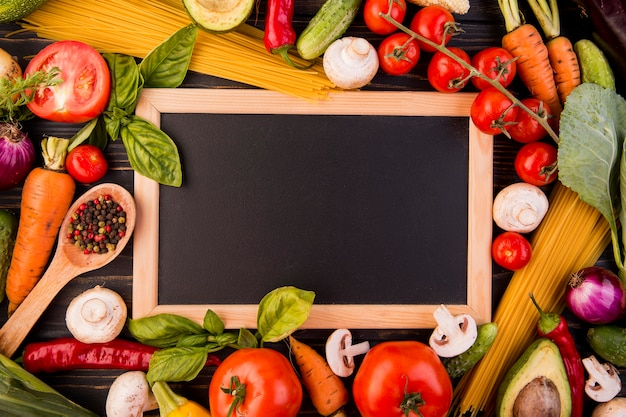 Top view assortment of different vegetables with blackboard